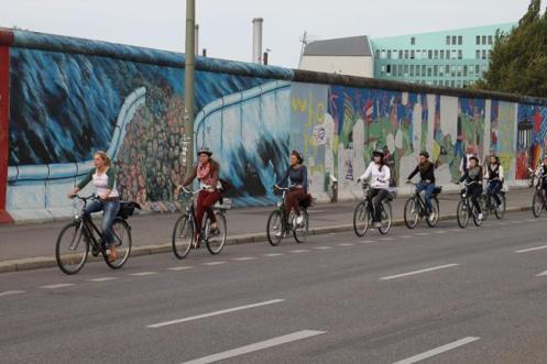 Grupo de ciclistas passeiam em um dos   trechos do pouco que restou do Muro de Berlim.
